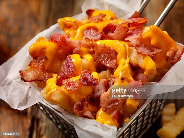 basket of bacon cheesy crinkle cut french fries - fries imagens e fotografias de stock