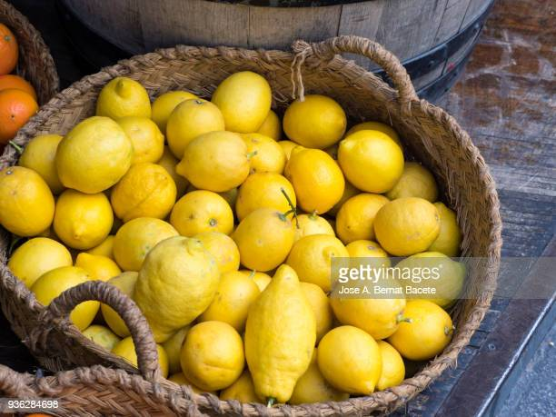 Basket of esparto grass with lemons for his sale on a market outdoor.