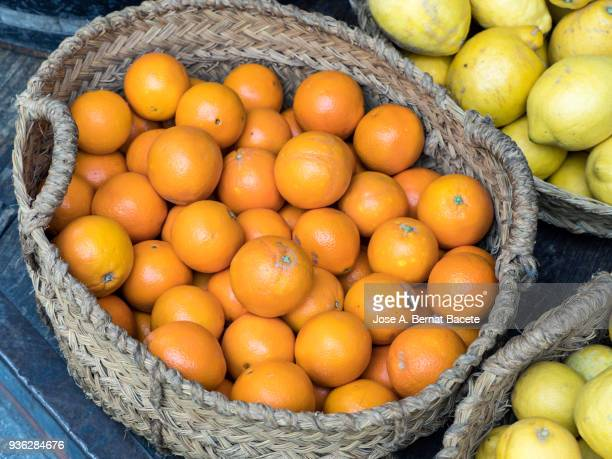 Basket of esparto grass with oranges for his sale on a market outdoor.