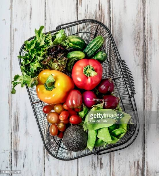 a basket of fresh fruits and vegetables on white background - フルーツ ストックフォトと画像