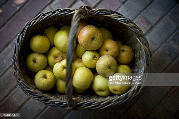 Basket of green apples on brick floor
