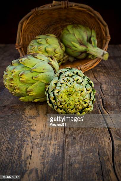 Basket of organic artichokes on wooden table