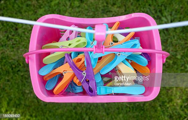 A basket of pegs hanging from a washing line