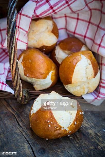 Basket of pretzel rolls on wooden table
