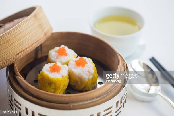 A basket of steamed shrimp and pork 'siu mai' dumplings with conpoy is arranged for a photograph at Lung King Heen restaurant at the Four Seasons...