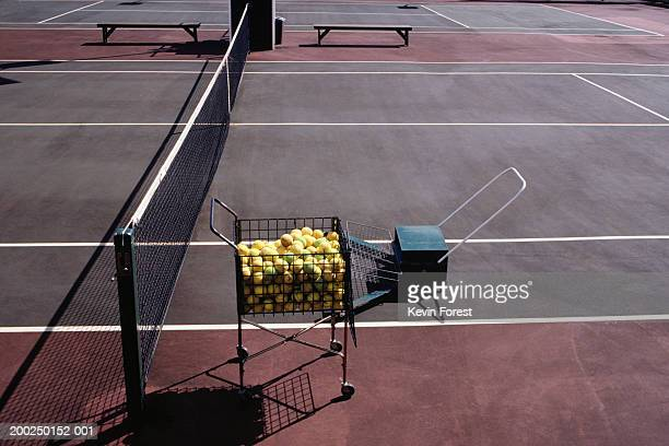 Basket of tennis balls on tennis court, elevated view