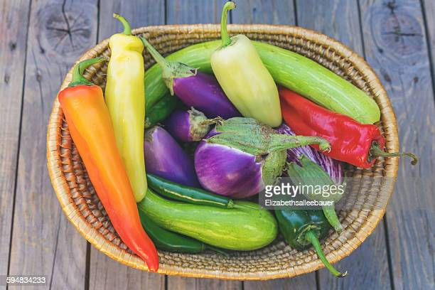Basket with fresh peppers and, aubergines, chilies and zucchini