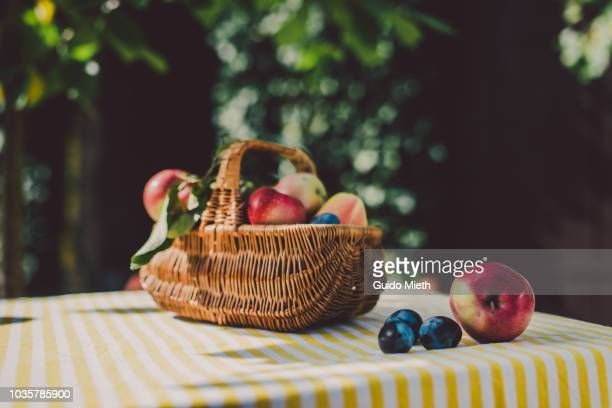 Basket with fruits on a table outdoor.