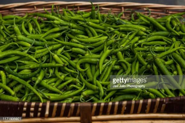 a basket with green chilli peppers in a market in san sebastian, basque country, spain - pais vasco fotografías e imágenes de stock