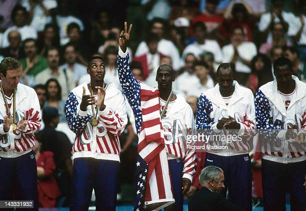 Summer Olympics: L-R: USA Larry Bird, Scottie Pippen, Michael Jordan, Clyde Drexler and Karl Malone victorious on podium with medals after winning...