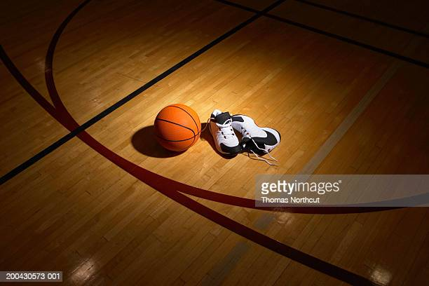Basketball and sports shoes on basketball court, elevated view