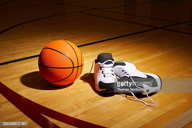 basketball and sports shoes on basketball court - basketball shoe stock photos and pictures