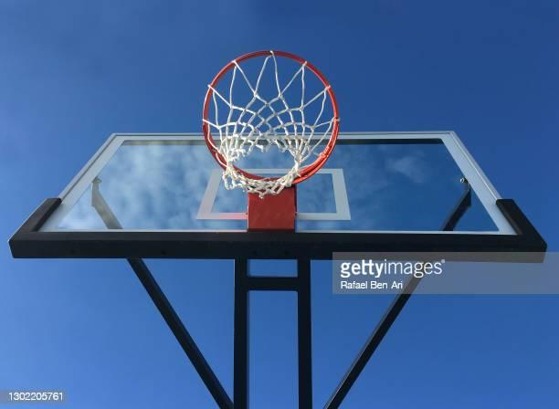 basketball backboard and hoop isolated on blue sky - rafael ben ari fotografías e imágenes de stock