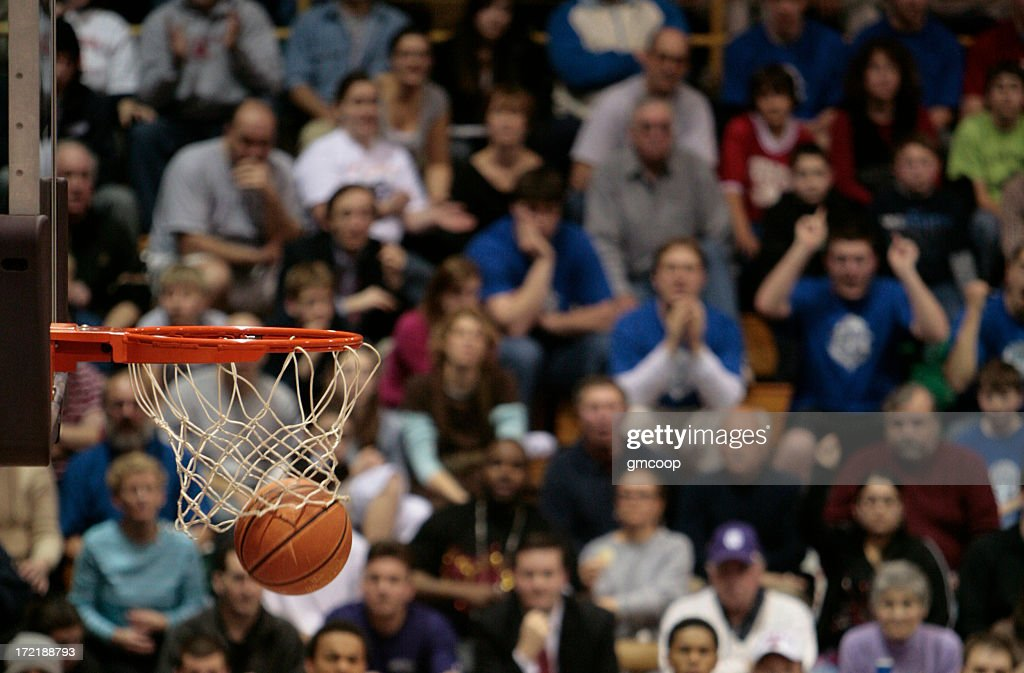 Basketball ball and backboard with fans in the background. : Stock Photo