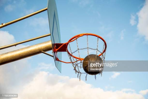 basketball ball in the basketball hoop - punkten stock-fotos und bilder