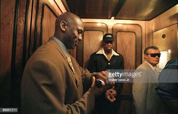 Casual portrait of Chicago Bulls Michael Jordan checking his watch with teammate Dennis Rodman and security personnel Sergeant Tom West in hotel...