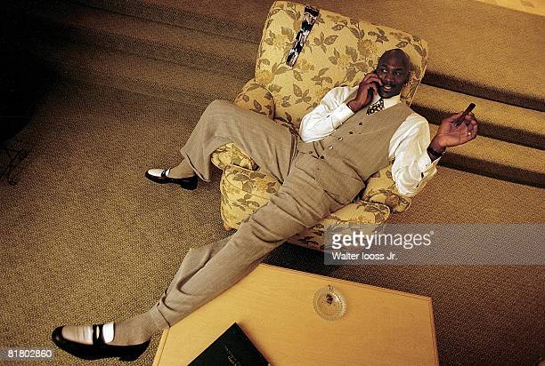Basketball Casual portrait of Chicago Bulls Michael Jordan talking on cellular phone and smoking cigar in hotel room Orlando FL 3/25/1998