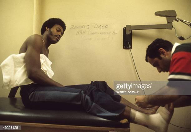 Casual portrait of Milwaukee Bucks Junior Bridgeman getting his feet taped by a trainer at Boston Garden Boston MA CREDIT Walter Iooss Jr