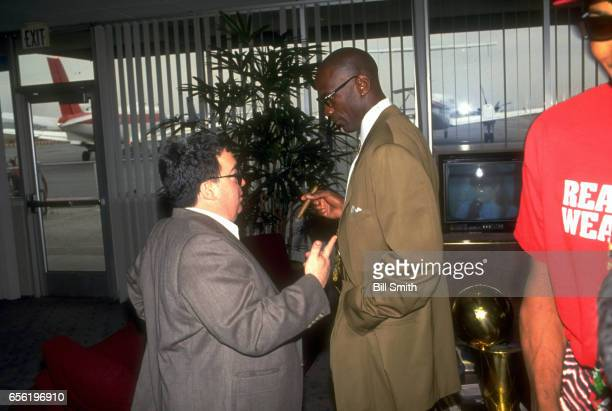 Chicago Bulls Michael Jordan talking with General Manager Jerry Krause in airport NBA championship trophy on table behind Jordan Los Angeles CA...