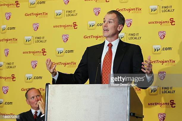 Basketball coach Andy Enfield addresses the audience as USC Athletic Director Pat Haden looks on during the press conference to introduce Enfield as...