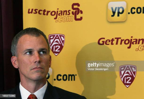 Basketball coach Andy Enfield looks on as USC Athletic Director Pat Haden addresses the audience during the press conference to introduce Enfield as...