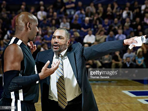 Basketball coach giving directions to player