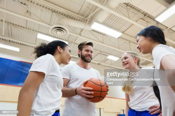 Basketball coach giving team talk to students in gym