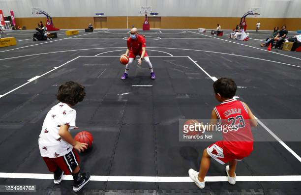 Basketball coach show kids how to dribble a ball at Dubai Sports World on July 08, 2020 in Dubai, United Arab Emirates. Dubai Sports World is the...