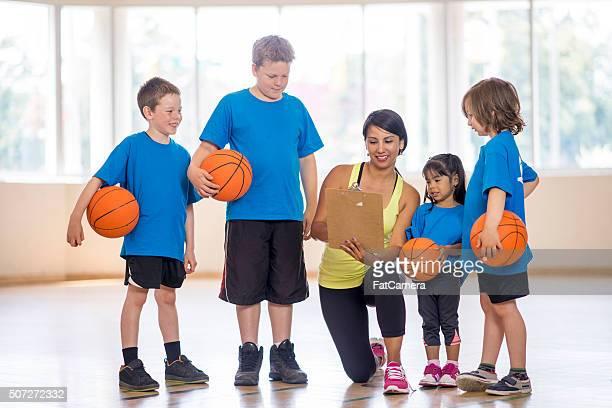 Basketball Trainer zeigen den Kindern ein Spiel