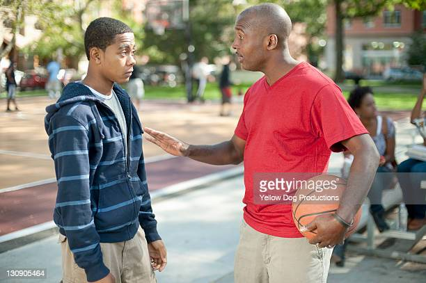 Basketball Coach talking to Teen boy