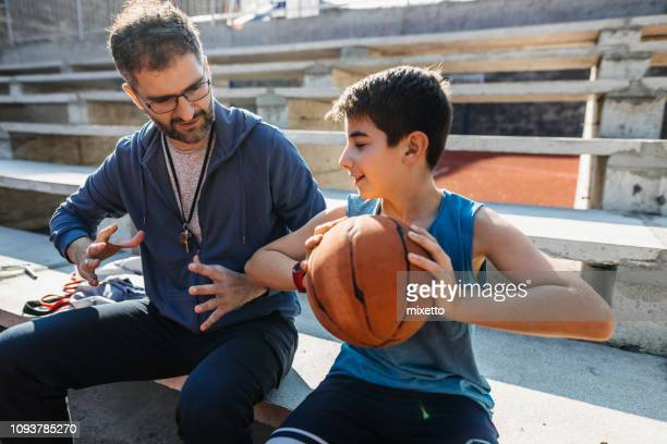 basketball coach with his young basketball player - basketball competition stock pictures, royalty-free photos & images