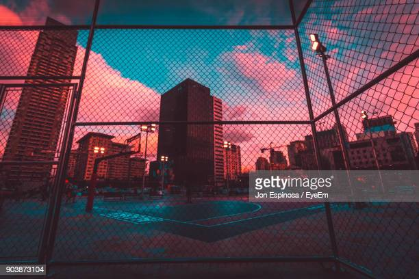 basketball court seen through fence in city during sunset - dämmerung stock-fotos und bilder