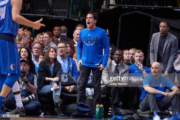 Dallas Mavericks owner Mark Cuban standing courtside with assistant vice president Michael Finley sitting during game vs Cleveland Cavaliers at...