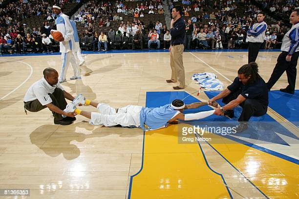 Basketball Denver Nuggets Allen Iverson lying on court and stretching with trainers before game vs New Jersey Nets Denver CO 1/27/2007