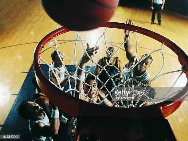 basketball falling through a basketball hoop with basketball players watching from the court - making a basket scoring stock pictures, royalty-free photos & images