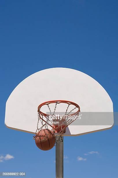 basketball falling through hoop - punkten stock-fotos und bilder