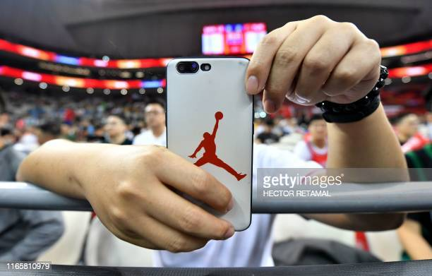 A basketball fan holds a smartphone with a logo of Michael Jordan before the start of a match between US and Turkey at the Basketball World Cup Group...