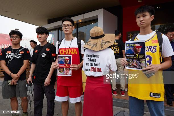 Basketball fans hold posters referencing comments by National Basketball Association Commissioner Adam Silver before attending an NBA preseason game...