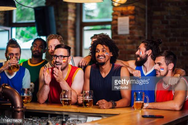 basketball fans watching game in a bar - world championship stock pictures, royalty-free photos & images