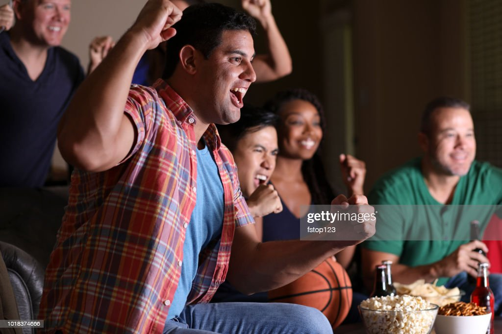 Basketball fans watching the game at home on television. : Stock Photo