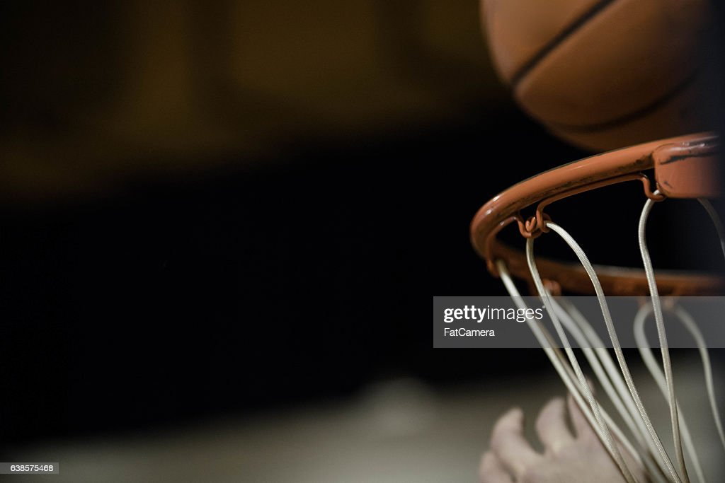 A basketball flying through the air and dropping into basketball hoop : Stock Photo