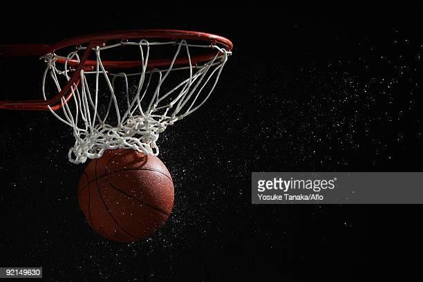 Basketball going through hoop against black background