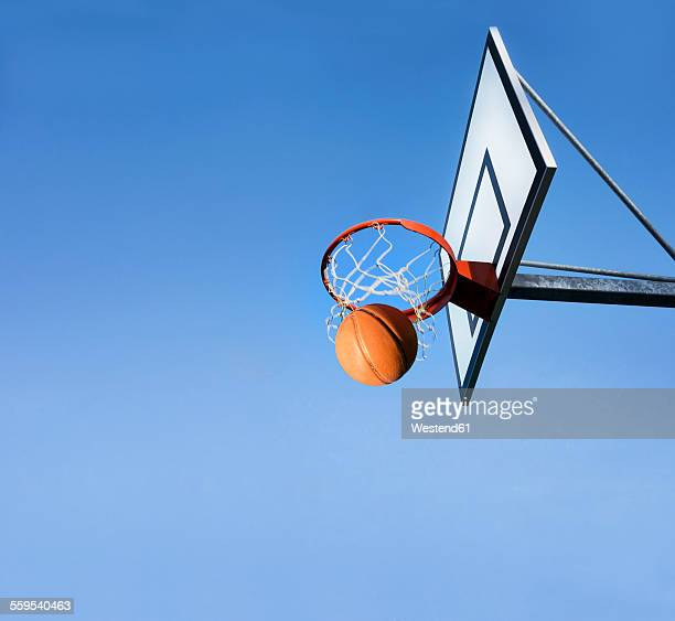 basketball going through hoop - basketball hoop stock pictures, royalty-free photos & images