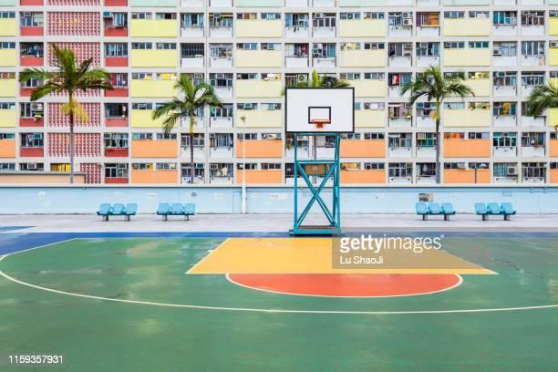 basketball ground with colorful facade of an apartment building in hong kong - courtyard - fotografias e filmes do acervo