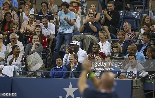 Basketball Hall of Famer Michael Jordan watches as Roger Federer of Switzerland plays against Marinko Matosevic of Australia at their men's singles...