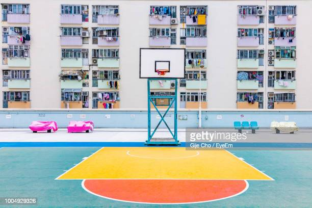 basketball hoop against buildings in city - basketball court stock pictures, royalty-free photos & images