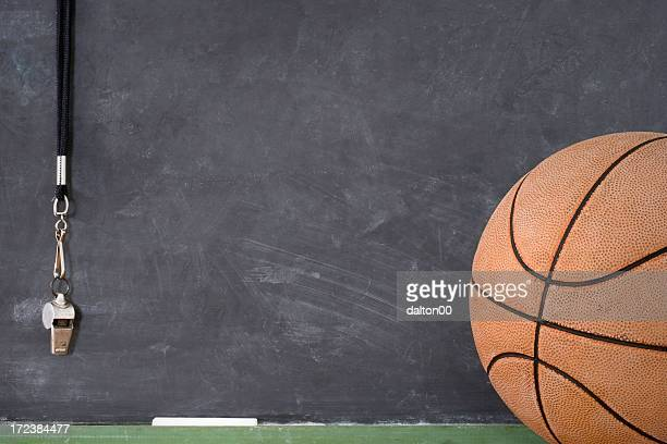 A basketball in front of a chalkboard and hanging whistle