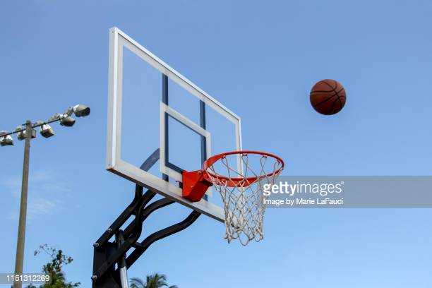 basketball in midair near basketball hoop outdoors - shooting baskets stock pictures, royalty-free photos & images