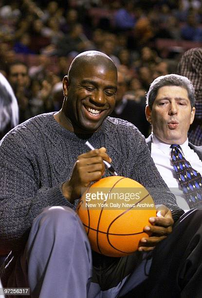 Basketball legend Earvin Johnson autographs ball for a fan while attending a game between the New Jersey Nets and the Portland Trail Blazers at the...