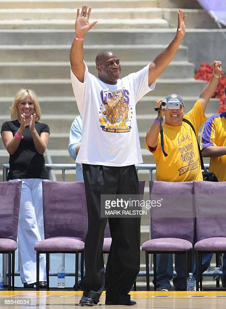 Basketball legend Magic Johnson waves as Los Angeles Lakers players celebrate during a victory parade at the Coliseum stadium in Los Angeles after...